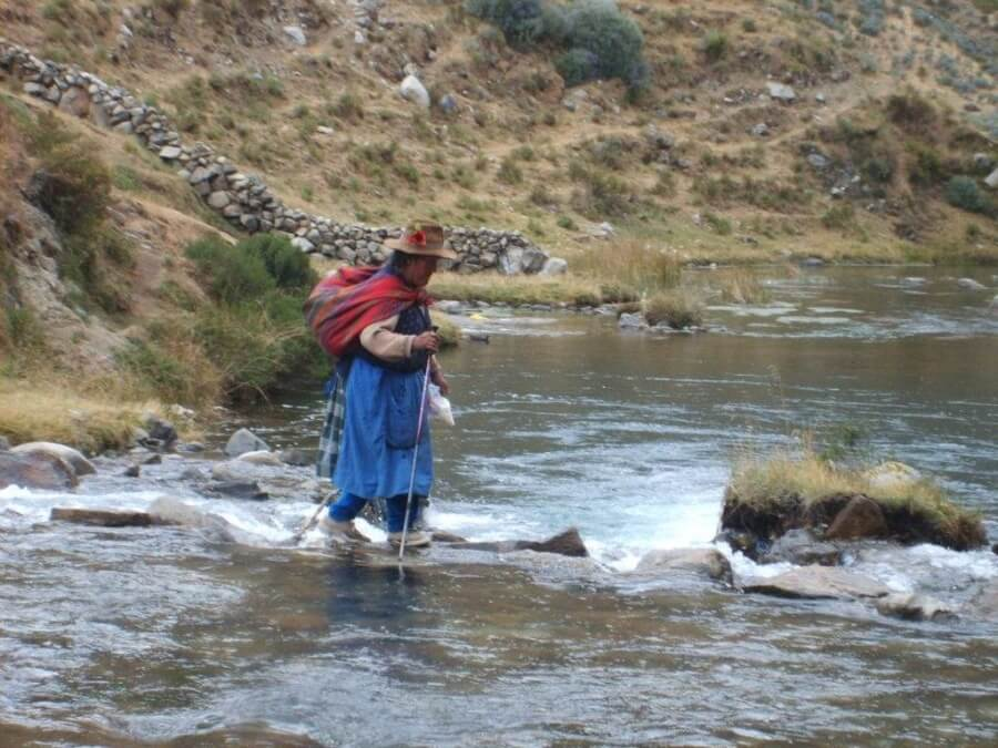 Local woman crossing river in Huaraz