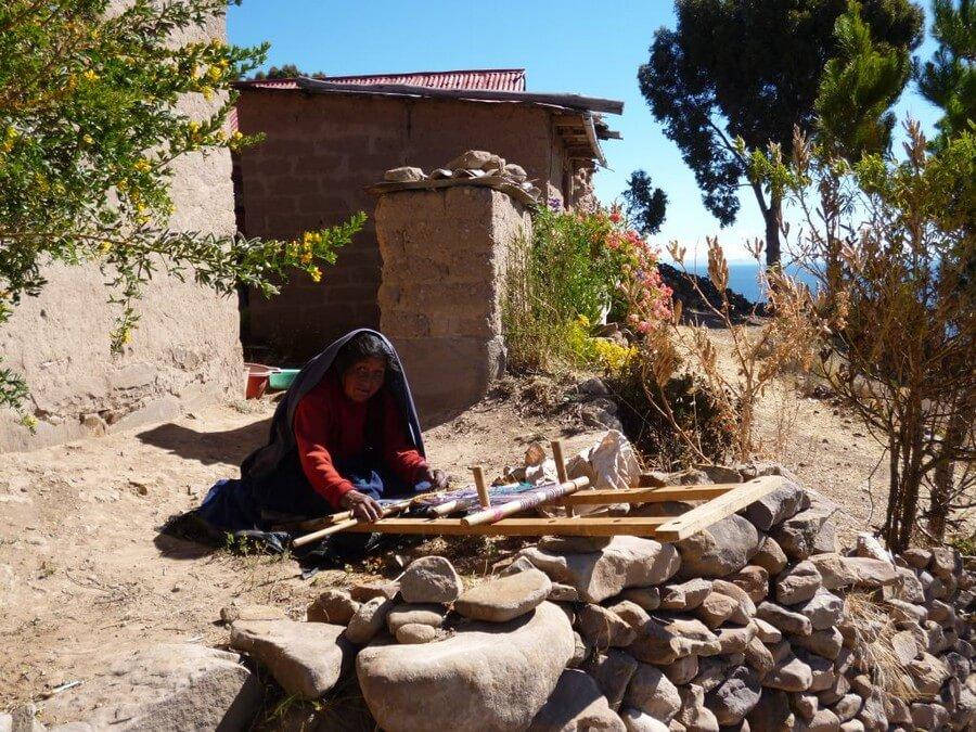Oude vrouw die aan het weven is op Taquile Island